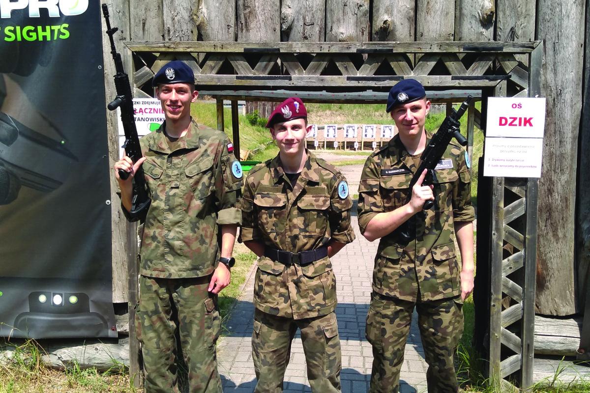 Zajęcia na strzelnicy - trzech uczniów pozuje z karabinkami